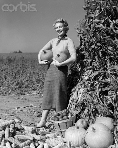 woman in the 1950s shopping for pumpkins at a roadside produce stand