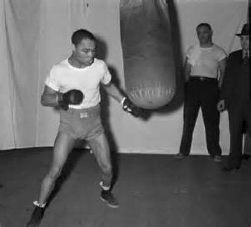 Henry Armstrong trains by hitting the heavy bag. (Pictured) Armstrong holds the record for the most welterweight title defenses.