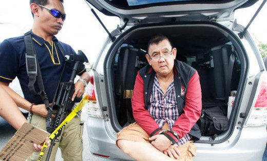 www.arabnews.com / A Philippine National Police Anti-Narcotics agent guards Robert Tan, one of four alleged drug traffickers who were arrested with six wooden crates of drugs worth $30 Million.