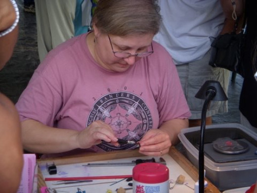 Hummingbird researcher, Linda Beall, fixes a band to the left leg of a Ruby-throated hummingbird.