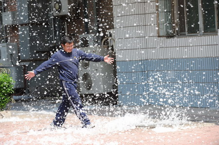 A man walks on the road as willow catkins fly in the air in a community in Beijing, April 13, 2009.