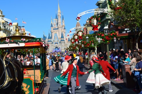 Christmas holiday dancers entertain guests on Main Street U.S.A in The Magic Kingdom at Walt Disney World. Cinderella's Castle is in the background.