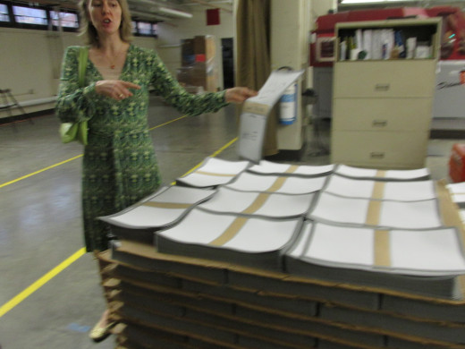 Darlene, our Tour Guide demonstrates the covers of Bibles before they are finally glued and bounded..
