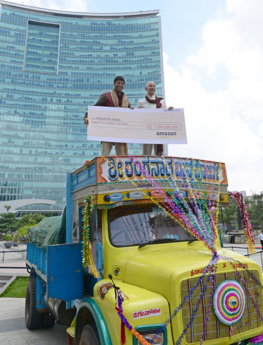 Jeff Bezos atop a lorry handing over a cheque to Amit Agarwal head of Amazon India.