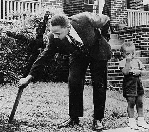 Rev. Martin Luther King Removing A Burnt Cross From His Lawn As His Son Watches