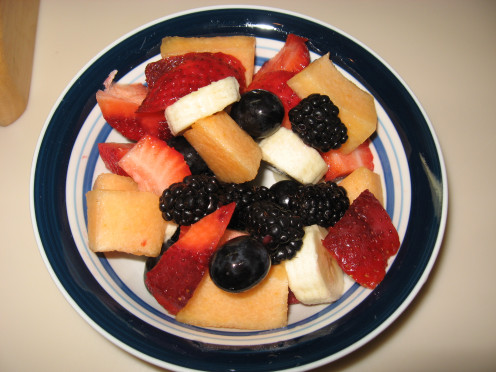 Look at the colorful fruits here: cantelope, strawberries, banana and blackberries.