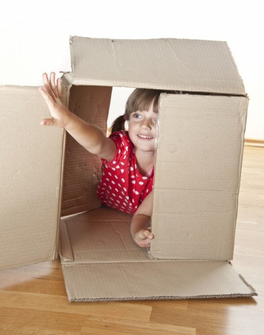 Little girl playing inside box