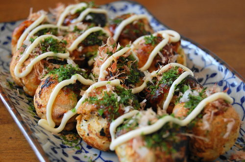 """Takoyaki is a Japanese snack in the shape of little round balls containing pieces of octopus.  Some may call it """"Octopus Balls"""" or """"Octopus Dumplings"""""""