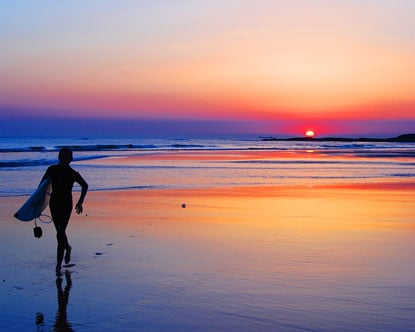 A surfer coming back from surfing, as the sun sets behind him.  The light reflected on the wet sand is beautiful.