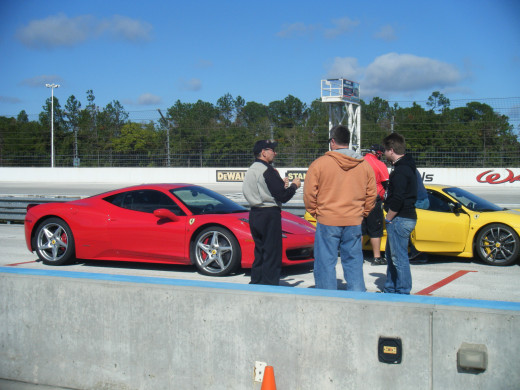 My dad and brother talking with their drive instructor in front of their Ferrari 548 Italia