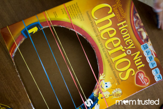 Cereal Box Guitar - Using a marker or pen, trace and cut out a large, oval shaped circle on an empty cereal box. Tape ends of box closed. Attach cardboard or stick handled to inside, secure with tape. Securely tape strings or rubberbands across hole.