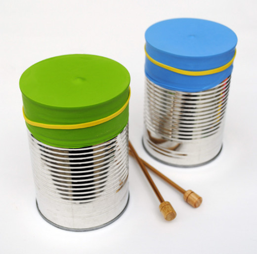 Coffee Can Bongos - Cover the base of an empty coffee can with colorful material, cut in an even shape. Secure with rubber band or string.  Use hands or kitchen utensils for sticks.