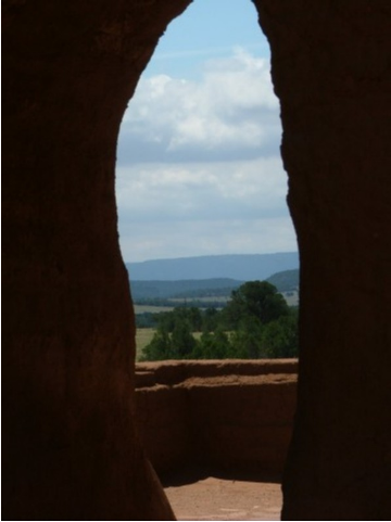 The remains of an arched doorway frames the plateau on which the mission stands in the Sangre de Cristo Mountains near Santa Fe, New Mexico.