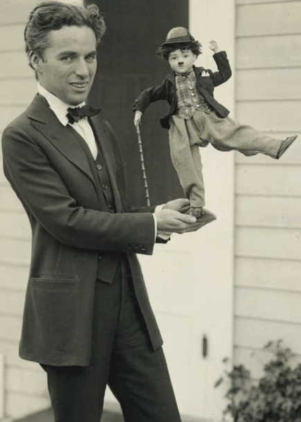 An antique Charlie Chaplin celebrity doll being held by the man himself.