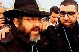 A Jew is interviewed on camera on Sunday 11th January 2015. The man with the arm around his shoulder is his Muslim friend