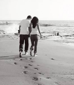 A couple walking on the beach holding hands.