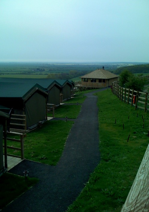 A view of Livingstone Lodge from the rangers tent. A rhino paddock on the right, for the wintertime, with tents on the left and the main part of the lodge ahead.
