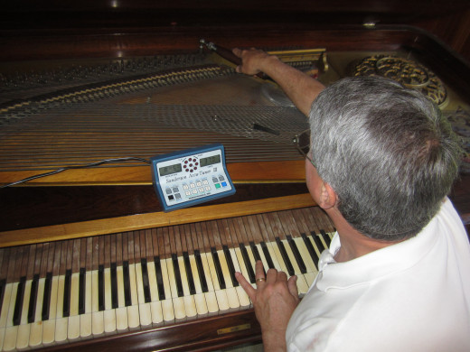 I don't know any piano player who would not appreciate a gift certificate for a piano tuning. This is Rick, the piano tuner extraordinaire giving my antique Emerson square grand a once over. This is a difficult instrument to tune, but Rick can do it!