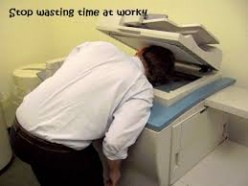 Goofing off? No. I got you. This man is resting by appearing to be working on a copy machine