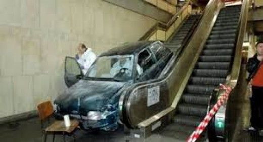 "This is a ""Master Time Waster."" He is letting the escalator take himand his car up to a higher floor"