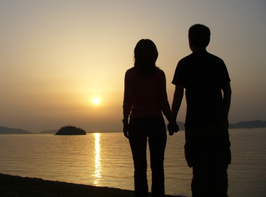 A Japanese couple savoring a romantic moment on the beach at sunset.