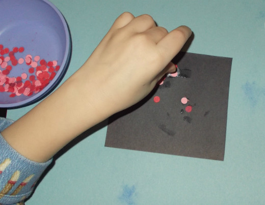 Kids can sprinkle designs on glue with a dot card.