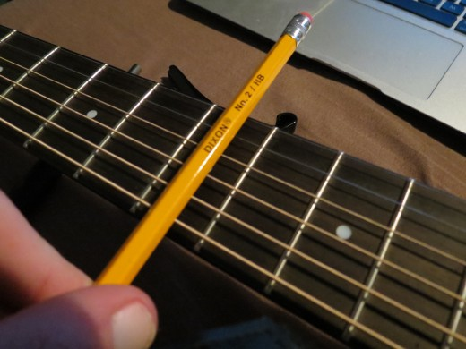 The pencil is placed over the 7th fret, as close to center as possible.