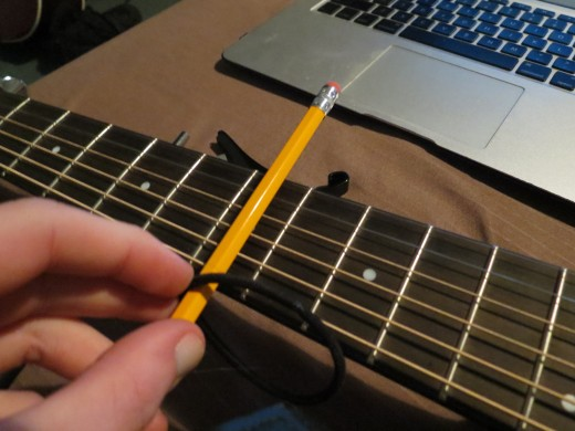 Start with the rubber band (in this case an elastic hair band) at the top of the pencil.