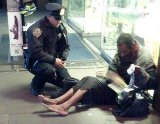 Police officer buys a shoeless man on streets some shoes on a cold night in New York City.