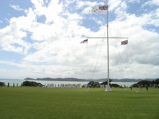 The flagstaff is flying (left – right) the Flag of the United Tribes of New Zealand, the Ensign of the Royal New Zealand Navy and the Union Flag.