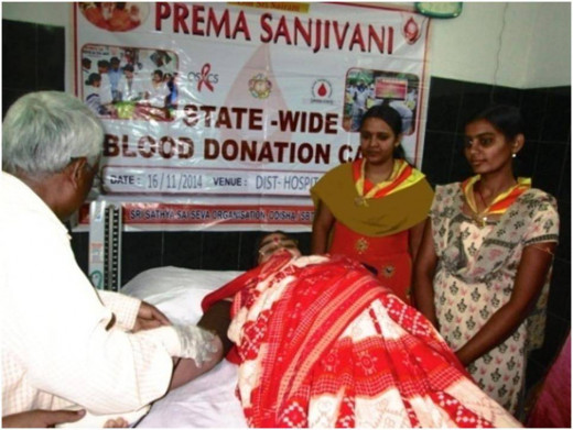 Una mujer dona sangre bajo la bandera Sai Sanjeevani.