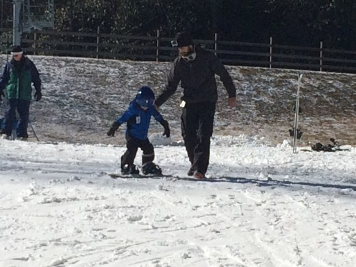 "Buddy is shown here ""snowboarding"" with Uncle Zach's help."