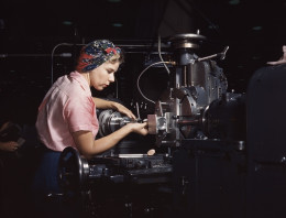 A woman uses a scarf as a turban to keep her hair out of her face and away from the machinery on the job.