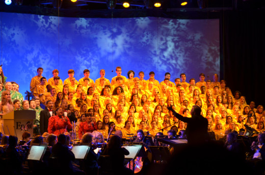 A 50-piece orchestra accompanies the mass choir and celebrity Jodi Benson as she narrates the Christmas story during the Candlelight Processional at Walt Disney World.