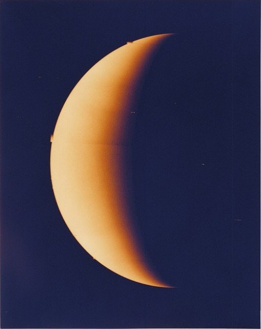 Venus crescent.  The planet is covered by an opaque layer of very reflective clouds of sulfuric acid, which means that its surface cannot be seen from space in visible light. It may have had oceans previously, but these have long since vaporized.