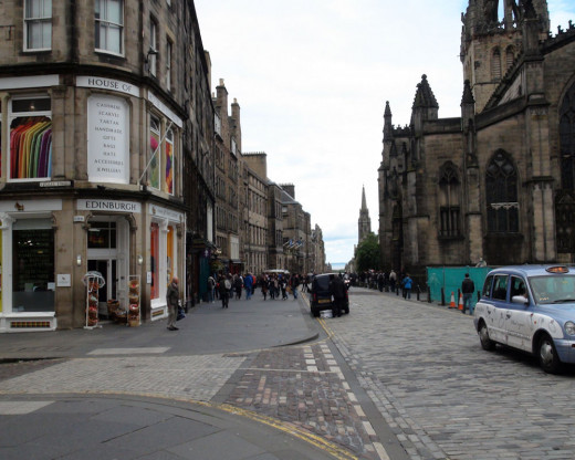 Edinburgh street view shows the historic architecture buildings that are still in use.  the pedestrian sidewalks are quite large in comparison to the amount of space offered to the automobiles.