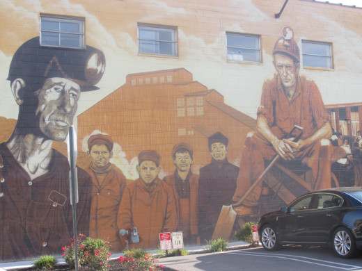 A mural of the coal miners on the side of a building.