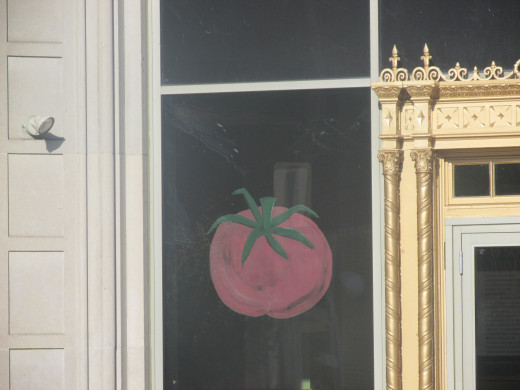 One of many tomatoes painted on windows in the town.