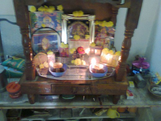 The wooden temple in puja room with Lakshminarayan idols in center and other images of Gods all decorated with flowers