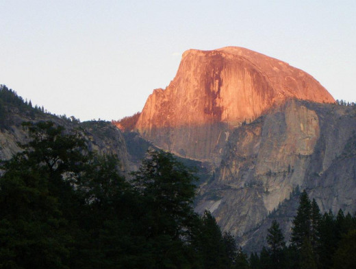 Half Dome, Yosemite is lit with a golden light because of the sunset causing it.