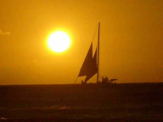 Background lighting makes a silhouette of a sailboat near Waikiki, HI