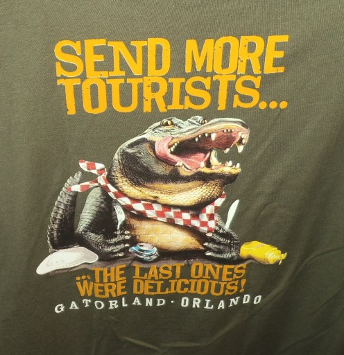 "Photo of a t-shirt from Gatorland. ""Send more tourists"" says the hungry alligator."