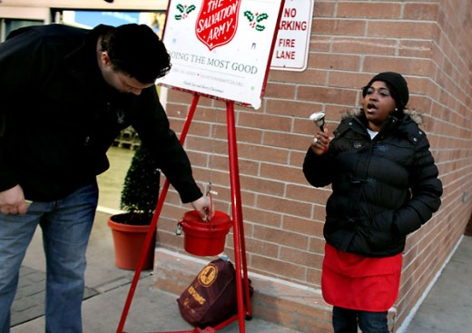 A  Salvation Army volunteer rings her bell outside a store in Virginia Beach as a donor slips a donation in the kettle. (Photo by David B. Hollingsworth | The Virginian-Pilot)