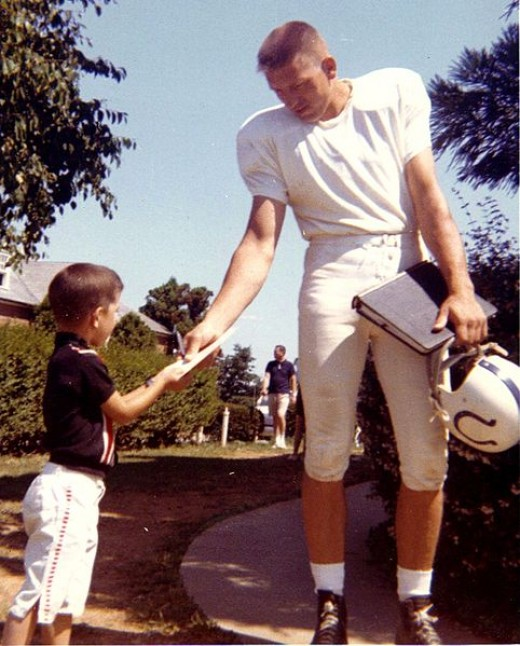 Johnny Unitas signing an autograph at the Baltimore Colts' Westminster training camp.