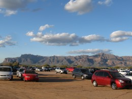 The parking lot is a dirt field with the mountains as a back drop
