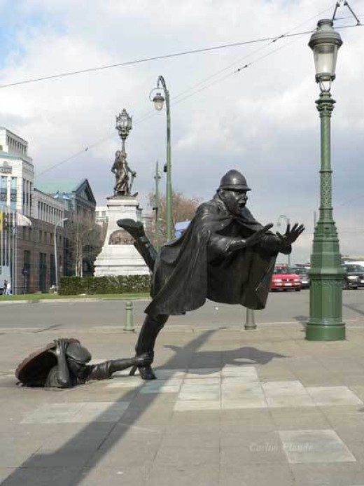 De Vaartkapoen(Brussels , Belgium) :   Low down, a young rebel, the Vaartkapoen, reminiscent of a jack-in-the- box, topples over a policeman higher up, thus overthrowing his authority.