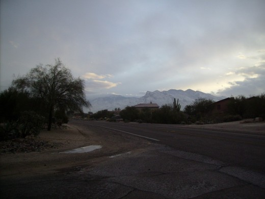 Early morning clouds lifting to reveal snow covered Santa Catalina Mountains on a cold January morning in Tucson