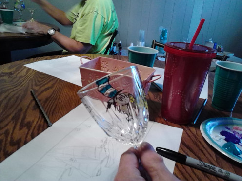 "Mike Van Natta, using his artistic hand at painting the face of ""Cat in the Hat"" on a wine glass during an Art & Wine Night, at Nearwood Winery."