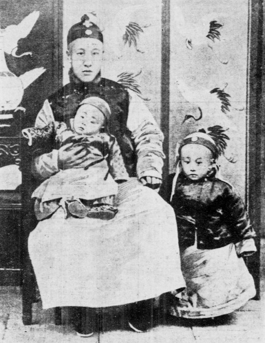 A three-year-old Puyi (right), standing next to his father (Zaifeng, Prince Chun) and his younger brother Pujie