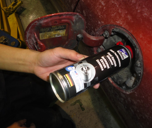 Adding fuel system cleaner to gas.